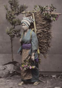 Woman in pastel colours carrying a heavy load